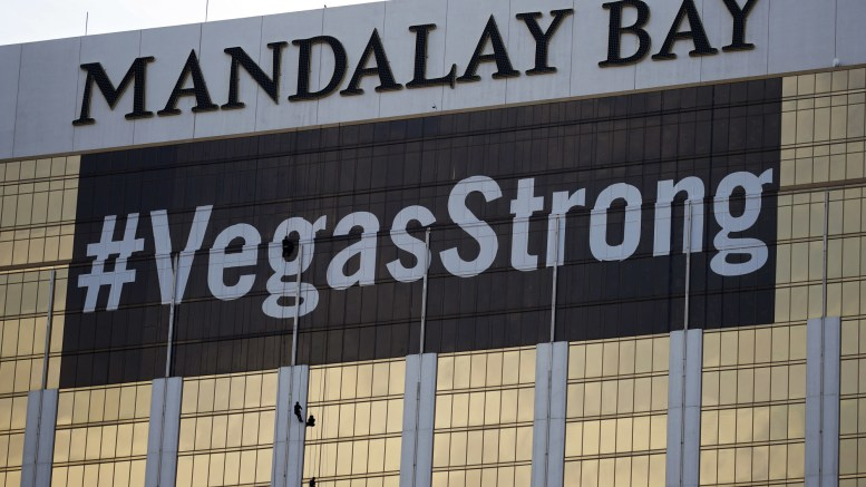Workers install a #VegasStrong banner on the Mandalay Bay hotel and casino Monday, Oct. 16, 2017, in Las Vegas. Stephen Paddock opened fire from the hotel on an outdoor country music concert killing dozens and injuring hundreds. (AP Photo/John Locher)
